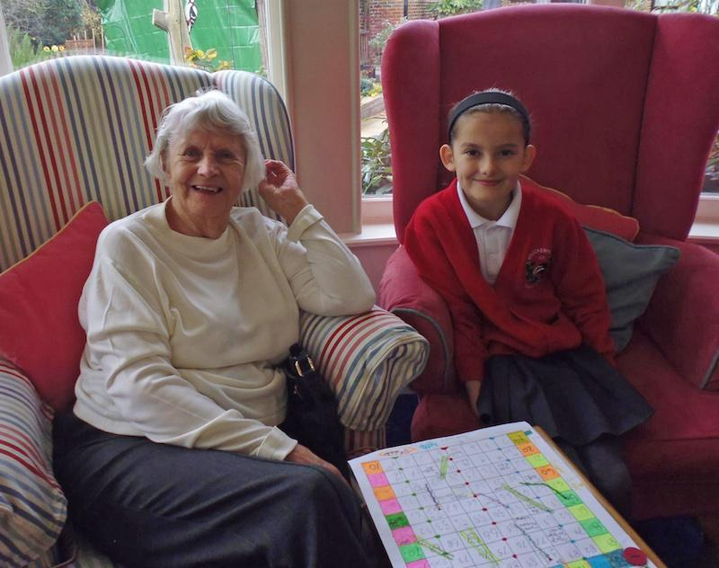 Enjoying a game of snakes and ladders at Woodpeckers care home in Brockenhurst