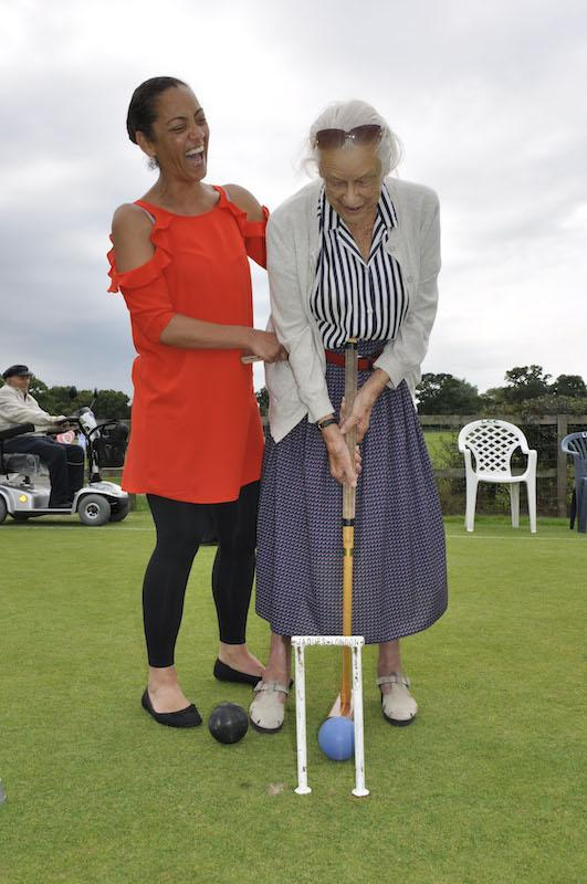 Court Lodge resident Eileen Simpson swings her mallet accompanied by Home Manager Sam Reid.